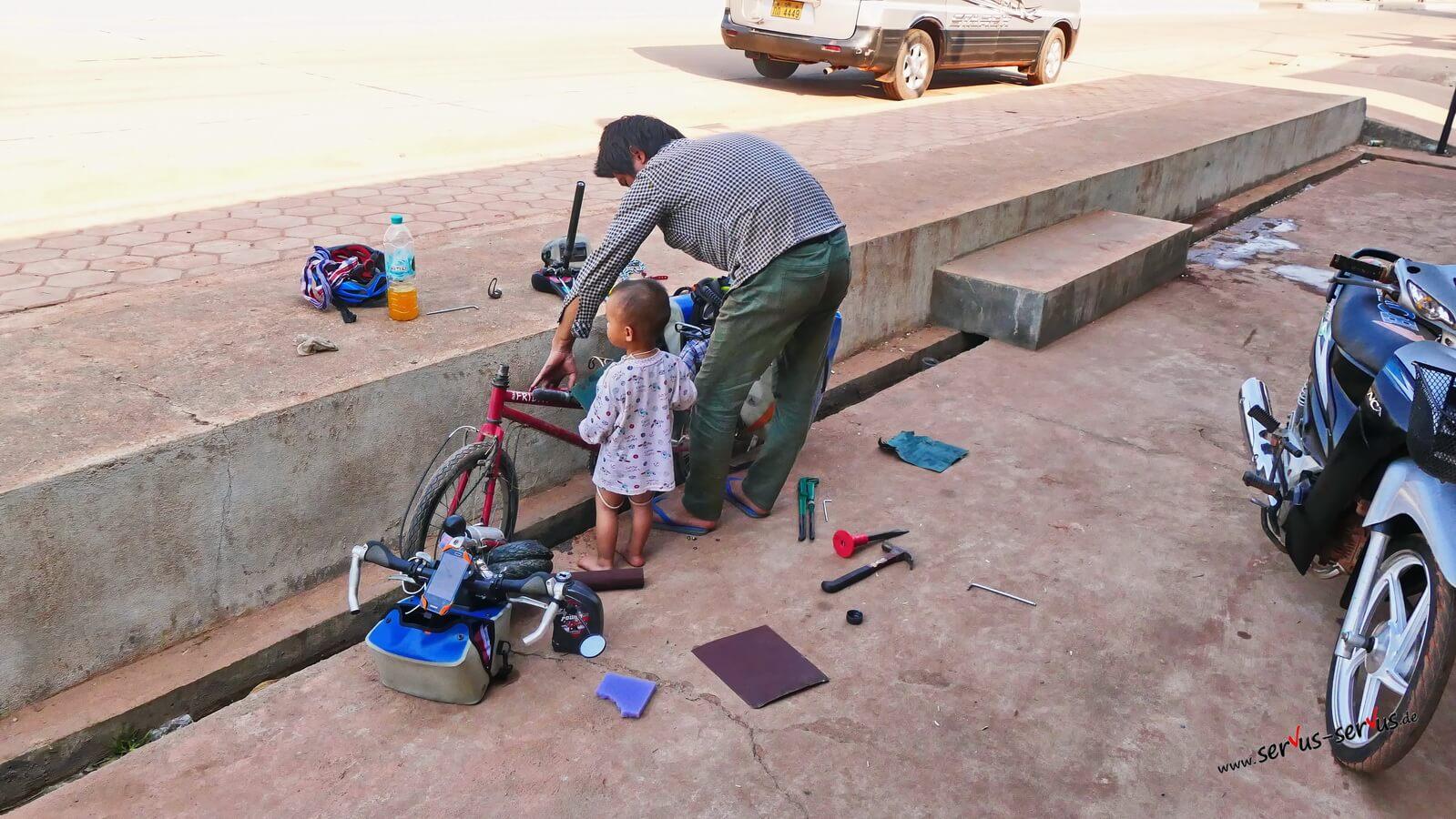 Fahrradreparatur am Straßenrand in Laos