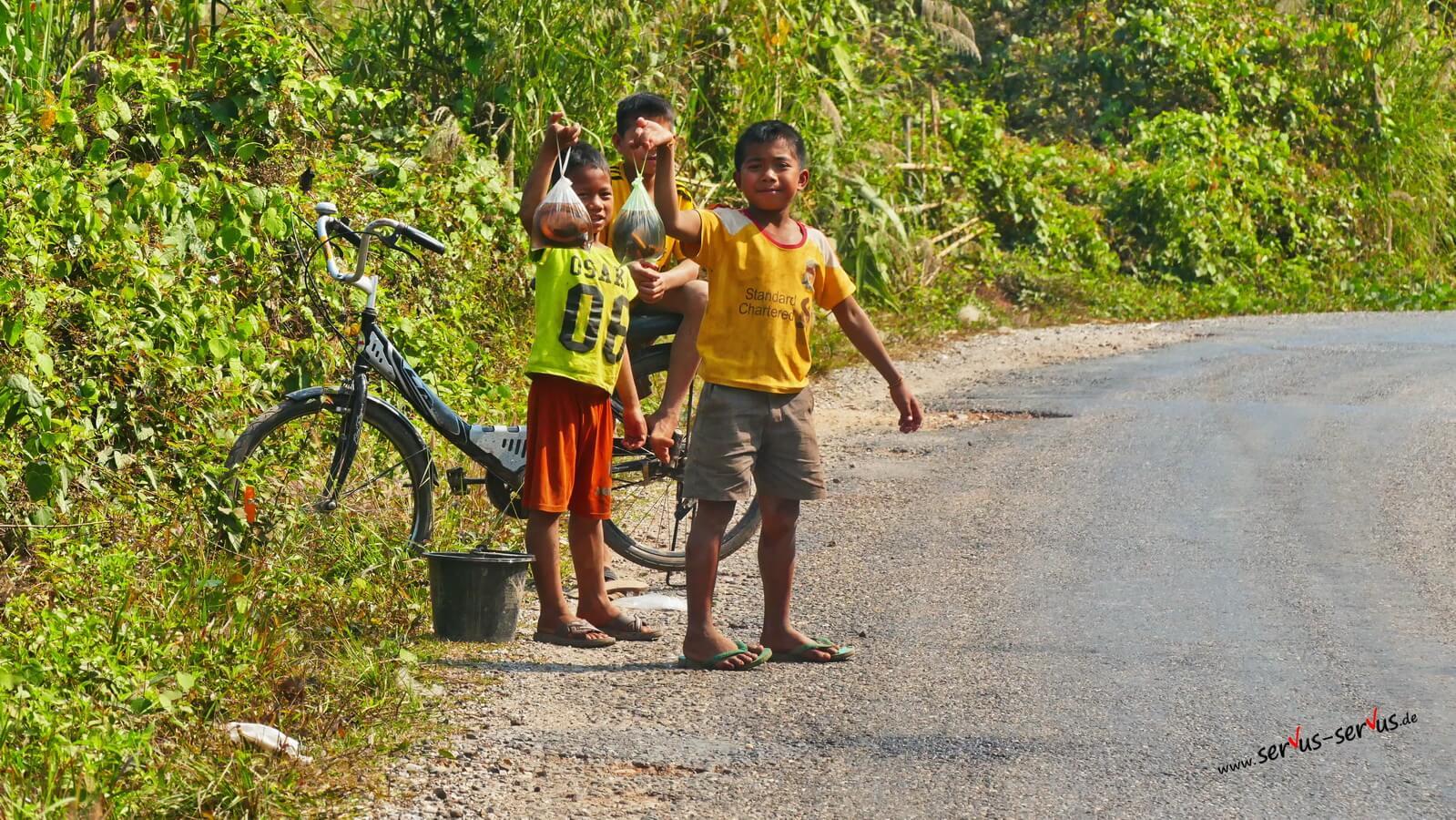 Kinder am Straßenrand verkaufen Fisch