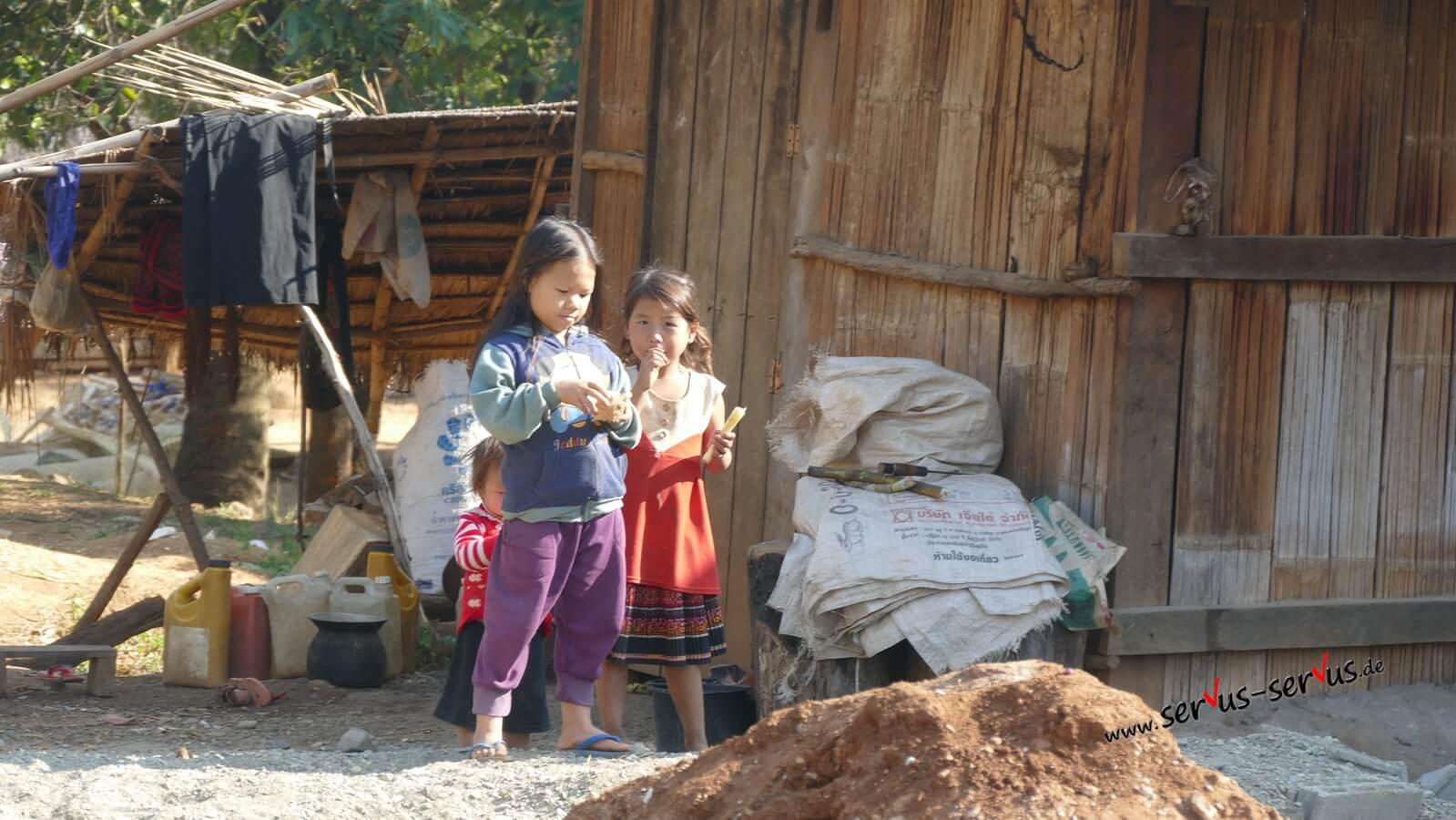 sawadee Kinder spielen am Straßenrand in Laos