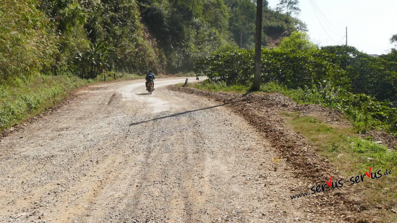 Straße in laos schotterweg mit moped