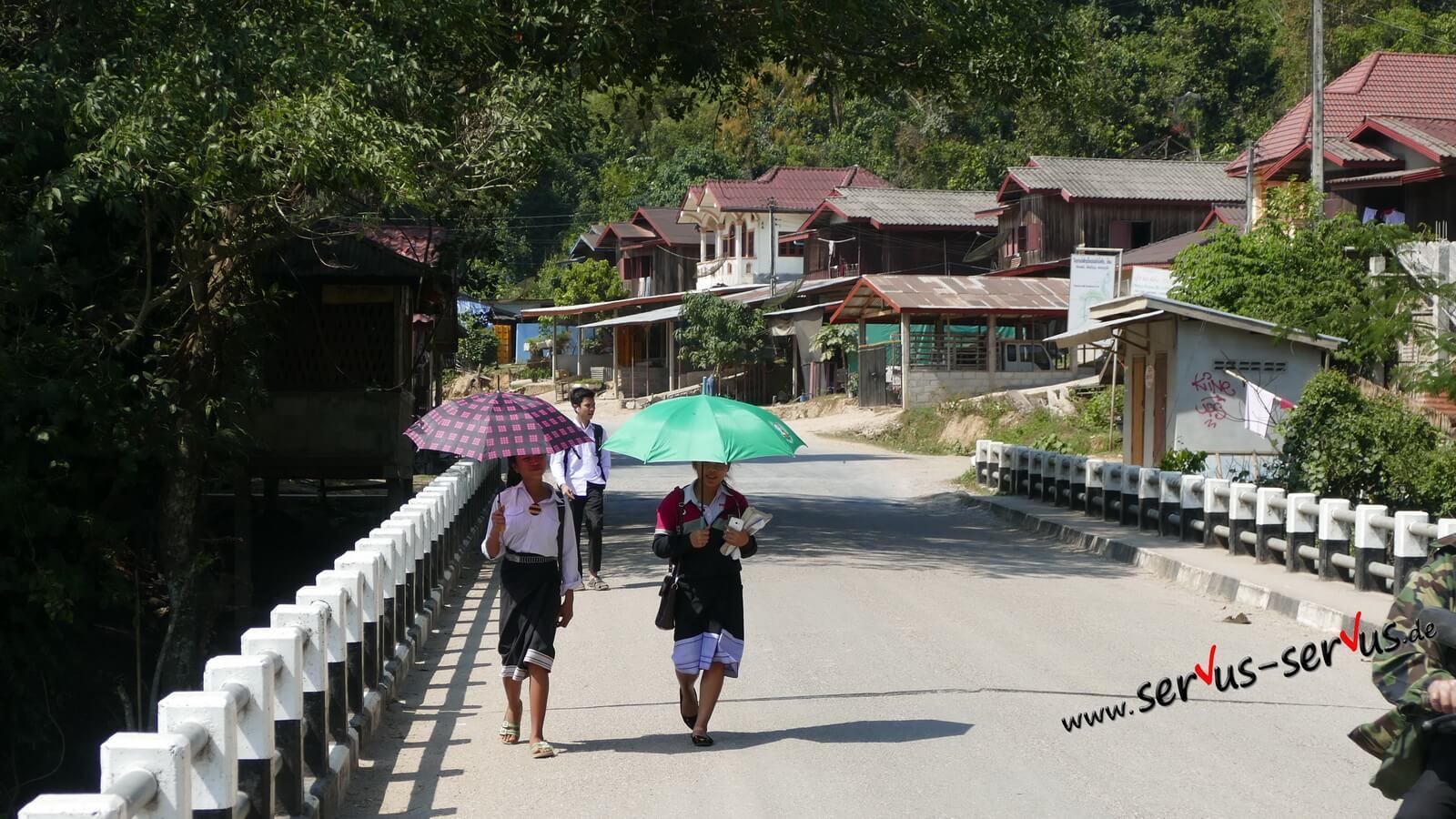 schulweg mit sonnenschirm in laos