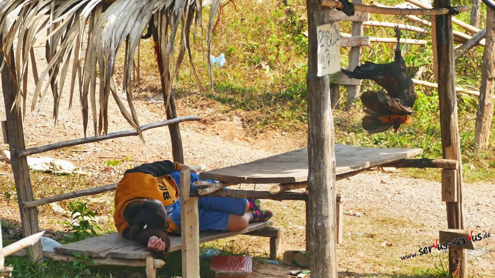 Frau schläft am Straßenrand in Laos