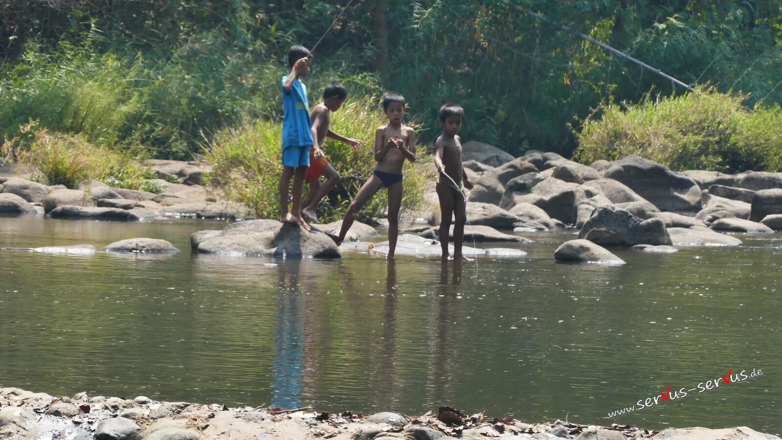 Tad Pasuam, Laos, Kinder beim angeln am Wasserfall