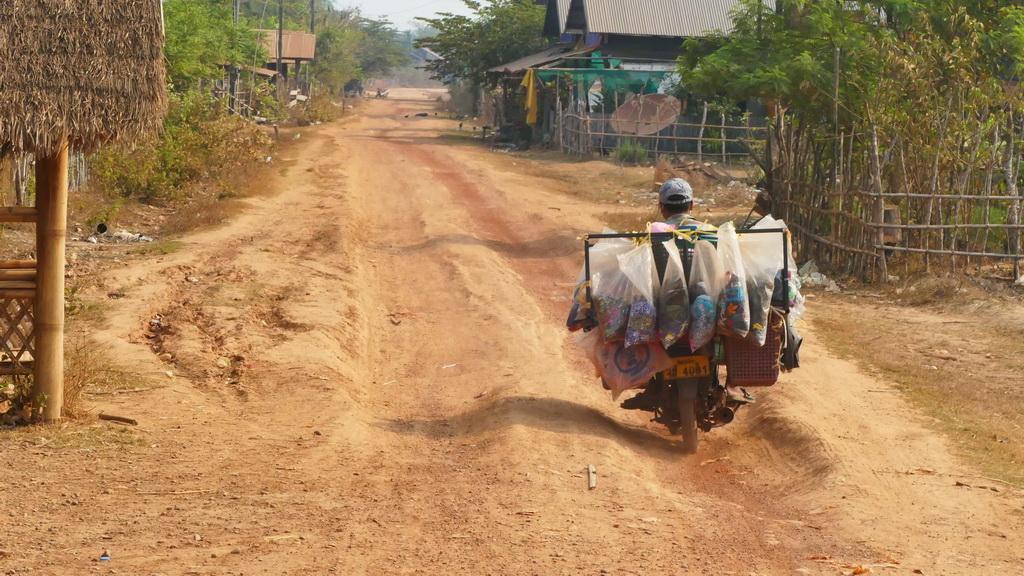 Motorad auf einer staubigen Buckelpiste in Laos
